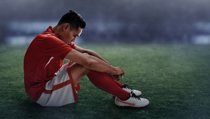 Dejected Footballer Sat on Pitch
