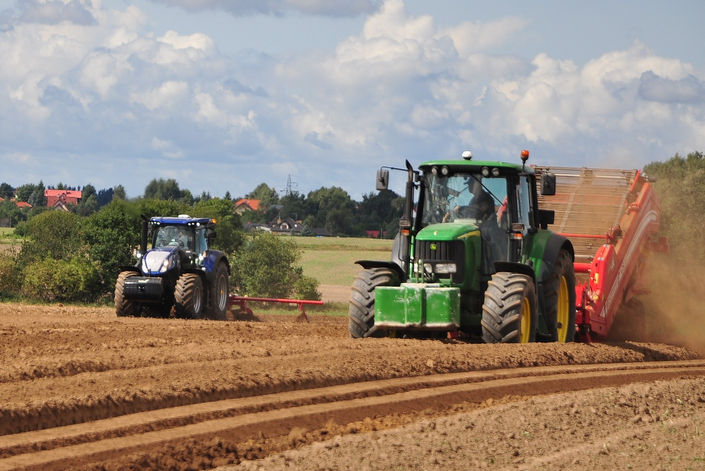 Green Tractor and Blue Tractor Ploughing Field