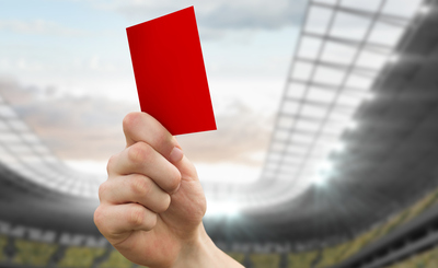 Red Card Being Shown in Football Stadium